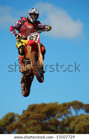 Motocross rider airborne with blue sky background