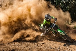 Motocross rider creates a huge cloud of dust and debris