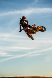 Motocross Rider Jump in a blue sky with clouds