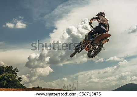 Motocross rider jumping in the air #556713475