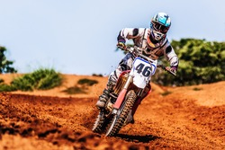 Motocross Rider Speeding Downhill in Mud Track
