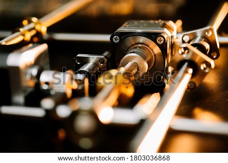 motor and guides for the laser machine. details of the engraving machine, black warm background, orange light Foto stock ©