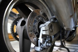 Motor bike brake calliper on the bike. Racing sport bike in a garage, workshop with used brakes.