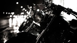 Motor bike headlight.Motorbike detail.Shiny chrome motorcycle.Closeup photo of motorcycle at night,active lifestyle,dangerous transport,journey and freedom concept.City traffic lights bokeh background