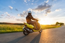 Motor biker riding on empty road with sunset light, concept of speed and touring in nature. Small motorcycle scooter