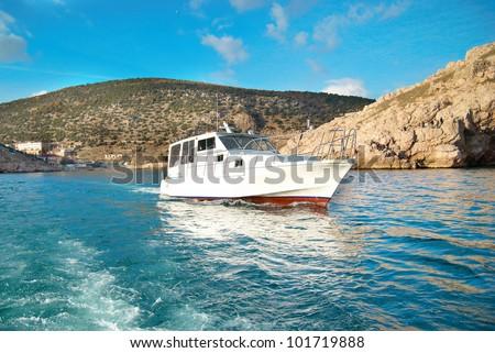 Motor boat cruising the sea near coast. Seascape