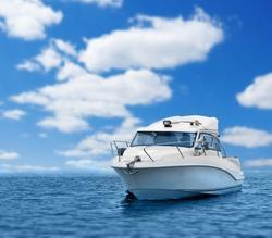 Motor boat in blue sea or ocean, cloud sky.
