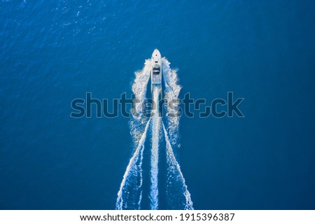 Motor boat in the sea. Aerial view luxury motor boat. Drone view of a boat sailing. Top view of a white boat sailing to the blue sea. Travel - image.
