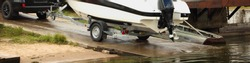 Motor boat launch, white vessel on trailer roll on concrete shipway to water