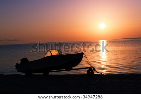 Motor boat on the beach at sunset