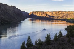 Motor boat on the beautiful lake at sunset. Billy Chinook lake in Oregon, USA, The Cove Palisades State park