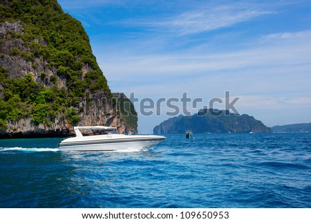 Motor boat on turquoise water of Maya Bay lagoon, Phi Phi island, Thailand - stock photo
