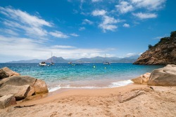 Motor boats and yachts moored in the sandy cove at Plage de Ficaghiola on the west coast of Corsica