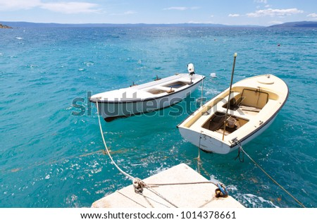 Motor boats drifting in the deep blue sea on Croatian coast.Adriatic Sea background.Crystal clear water,good sunny weather.Beautiful blue lagoon for summer vacation trip