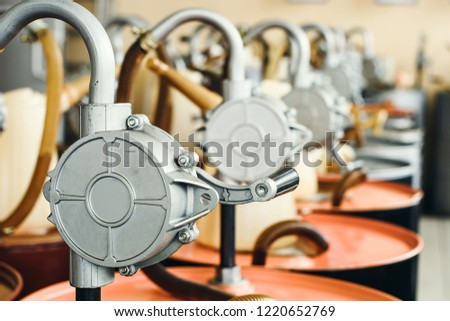 Motor oil in barrels with pump indoors with copy space. Store of lube. Product for bottling close up. Maintenance. Warehouse inside. Background of automotive shop. Auto service. Change of oil.