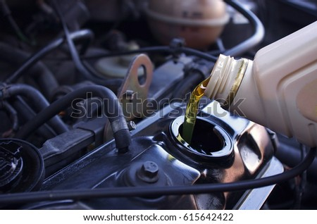 Motor oil pouring to car engine. Crude Oil Prices