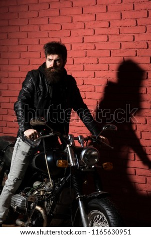 motor salon. bearded man with bike in motor salon. motor salon services. man in motor salon or repair shop. man at his bike #1165630951