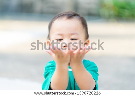 Motor skills and Fine Motor Skills Concept.Little baby boy child showing hands when he play sand in playground park.Child development concept.