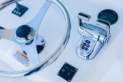 Motor yacht control panel. Steering wheel, gear levers, control button tachometer. Luxury yacht navigation bar.