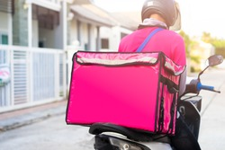 Motorbike delivery man wearing pink uniform and ready to send food.Delivering Food In City.Delivery man of takeaway with isothermal food pink case box driving find home.Express food delivery service.
