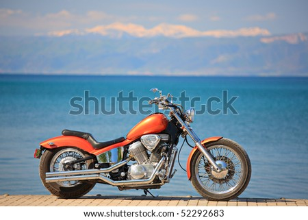 Motorbike on a shore of a lake - stock photo