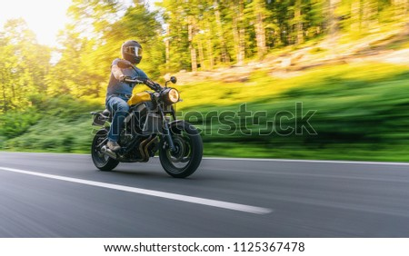 motorbike on the forest road riding at sunset. having fun driving the empty road on a motorcycle tour journey. copyspace for your individual text. #1125367478