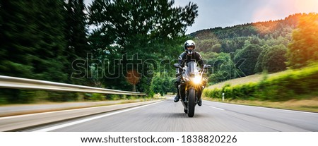 motorbike on the road riding. having fun driving the empty road on a motorcycle tour journey. copyspace for your individual text. Fast Motion Blur effect