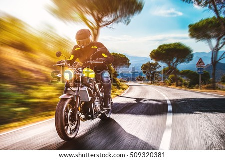 motorbike on the road riding. having fun driving the empty road on a motorcycle tour journey. copyspace for your individual text. #509320381