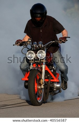 Motorbike rider on custom bike burning back tire and creating smoke