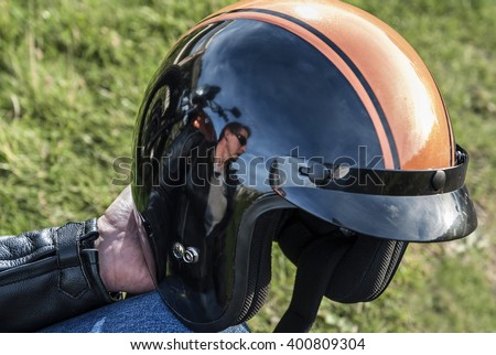 Motorbiker holding retro helmet with reflection of biker, motorbike, countryside and blue sky stock photography