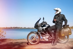 Motorbiker travelling, autumn day, motorcycle off road, rider, adventurer, extreme tourism, cold weather clothes, near the lake, light tinting, uses smartphone, internet, search,