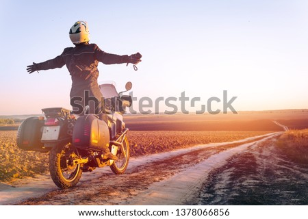 Motorbiker travelling, autumn day, motorcycle off road, the driver stands with open arms to the side, to meet a new day, adventurer, extreme tourism, cold weather clothes, light tinting