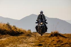 Motorbiker travelling in autumn mountains