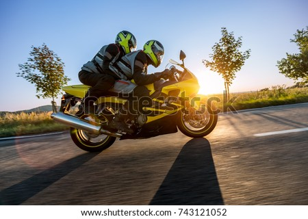 Motorbikers on sports motorbike riding in sunset. Outdoor photography, European landscape. Travel and sport photography. Motorbike is manufactured and designed in Japan #743121052