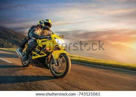 Motorbikers on sports motorbike riding in sunset. Outdoor photography, European landscape. Travel and sport photography. Motorbike is manufactured and designed in Japan