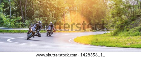 motorbikes on the forest road corner. having fun driving the empty road on a motorcycle tour journey. copyspace for your individual text.