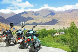 Motorbikes with beautiful sky, clouds, Himalaya mountains view background. Motorcycle trip in Leh, Ladakh, India. Traveling along Asia, Lifestyle sport Travel vacations outdoor concept.