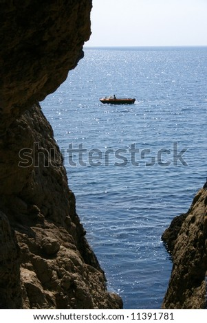 motorboat sails seaborne, is seen from cave