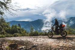 motorcycle adventure on the summit of the mountain, enduro, off road, beautiful view, danger road in mountains clouds, rider, dual sport