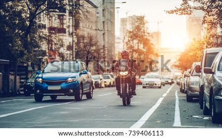 Motorcycle and cars are riding on street. City during the sunset.