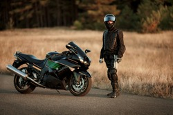Motorcycle driver in a helmet and leather jacket stands on the road next to a sports motorcycle