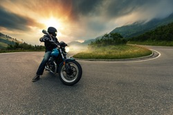 Motorcycle driver posing in Alpine landscape. Lifestyle photo with motion blur effect.