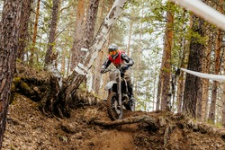 motorcycle enduro racing motocross in forest downhill