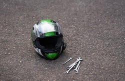 Motorcycle helmet at ground and some wrenches. Wrench at ground