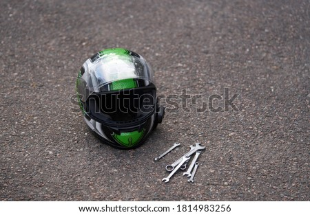 Motorcycle helmet at ground and some wrenches. Wrench at ground Stockfoto ©