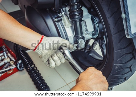 motorcycle Mechanic using impact wrench socket Replace rear shock absorber on big scooter in garage, (maintenance) selective focus