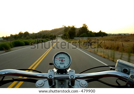 Motorcycle moving on a straight road from rider's perspective