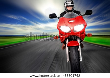 Motorcycle moving very fast along motion blurred road - stock photo