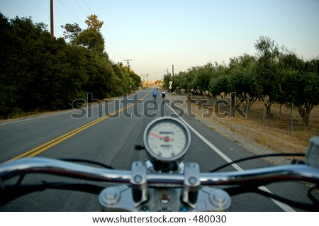 Motorcycle on road from rider's perspective with cyclists ahead. Shallow DOF, focus on cyclists.