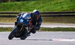 Motorcycle practice leaning into a fast corner on track. Sport Biker Racing on Road